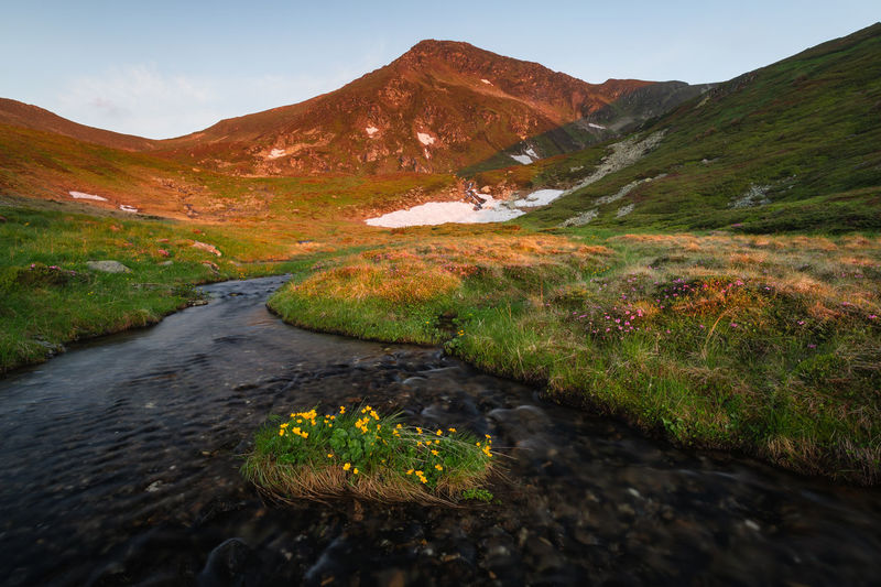Scenic view of stream flowing amidst mountains against sky