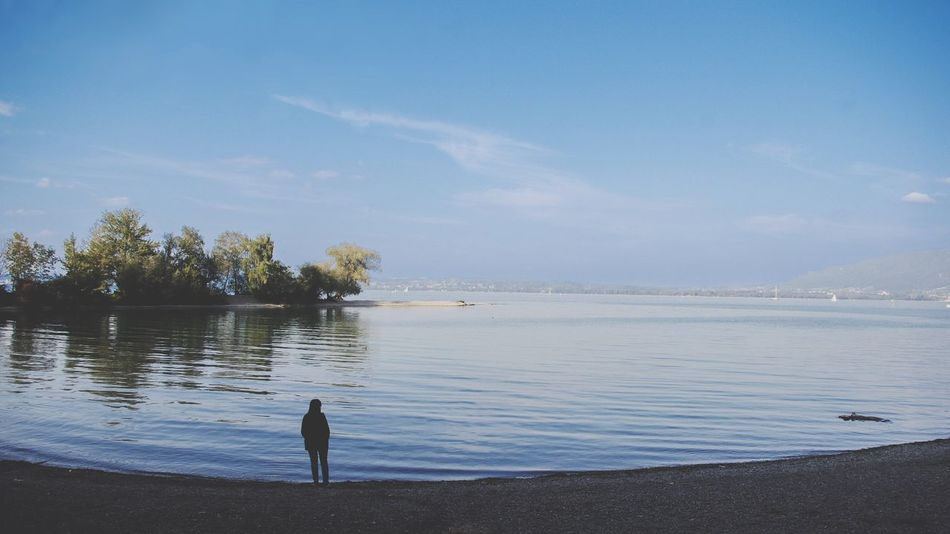 Woman standing by the lake Water Sky Nature Scenics Beauty In Nature Day Outdoors Lake Cloud - Sky Tranquil Scene One Person One Woman Only Standing Silhouette Loneliness Solitude Calm Quiet Moments Waves Copy Space Space For Copy Space For Text Miles Away The Great Outdoors - 2017 EyeEm Awards