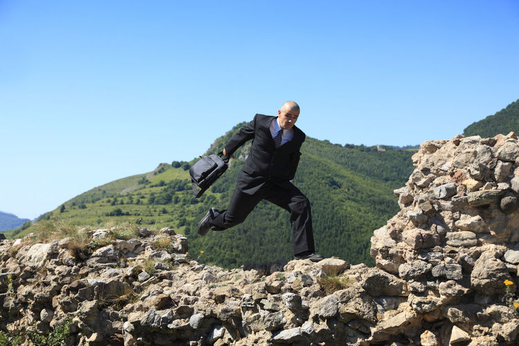 Portrait Of Businessman With Suitcase Running On Rock Formation