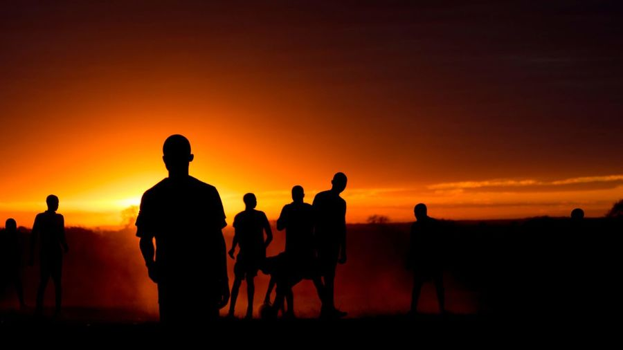 Silhouette people plying on land against clear sky during sunset