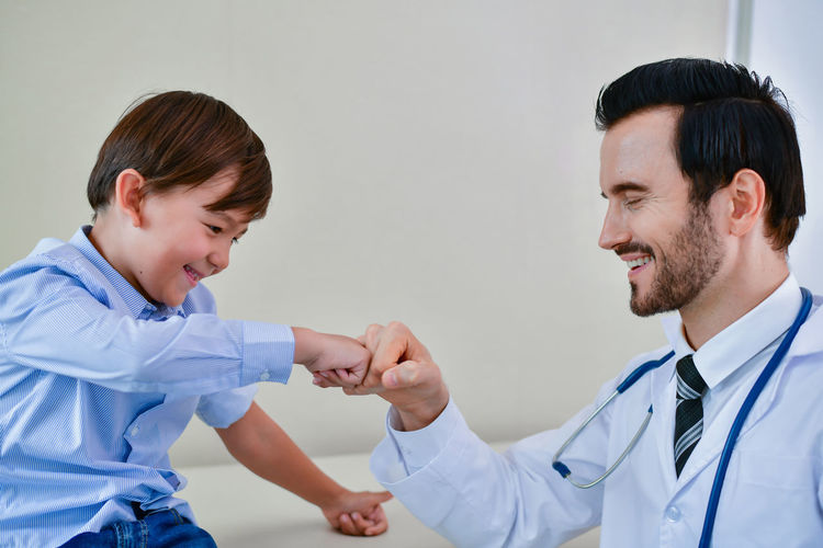 Cheerful Doctor And Boy Bumping Fist At Hospital