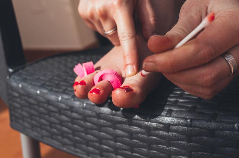 Cropped image of woman applying nail polish