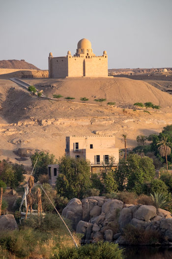 Mausoleum of Aga Khan, built in 1957, on a hill overlooking the Nile and Elephantine Island (in the foreground). In Aswan, Egypt Aga Khan Architecture Aswan, Egypt Building Exterior Dawn Desert Egypt Elephantine Island History Mausoleum Nature Nile No People Outdoors River Tomb