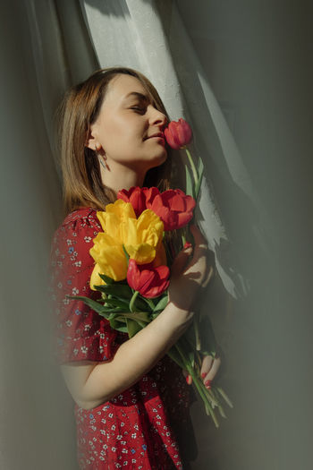 Beautiful young woman standing by red flower