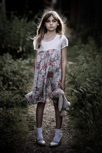 Portrait Of Girl Holding Stuffed Toy And Standing On Field