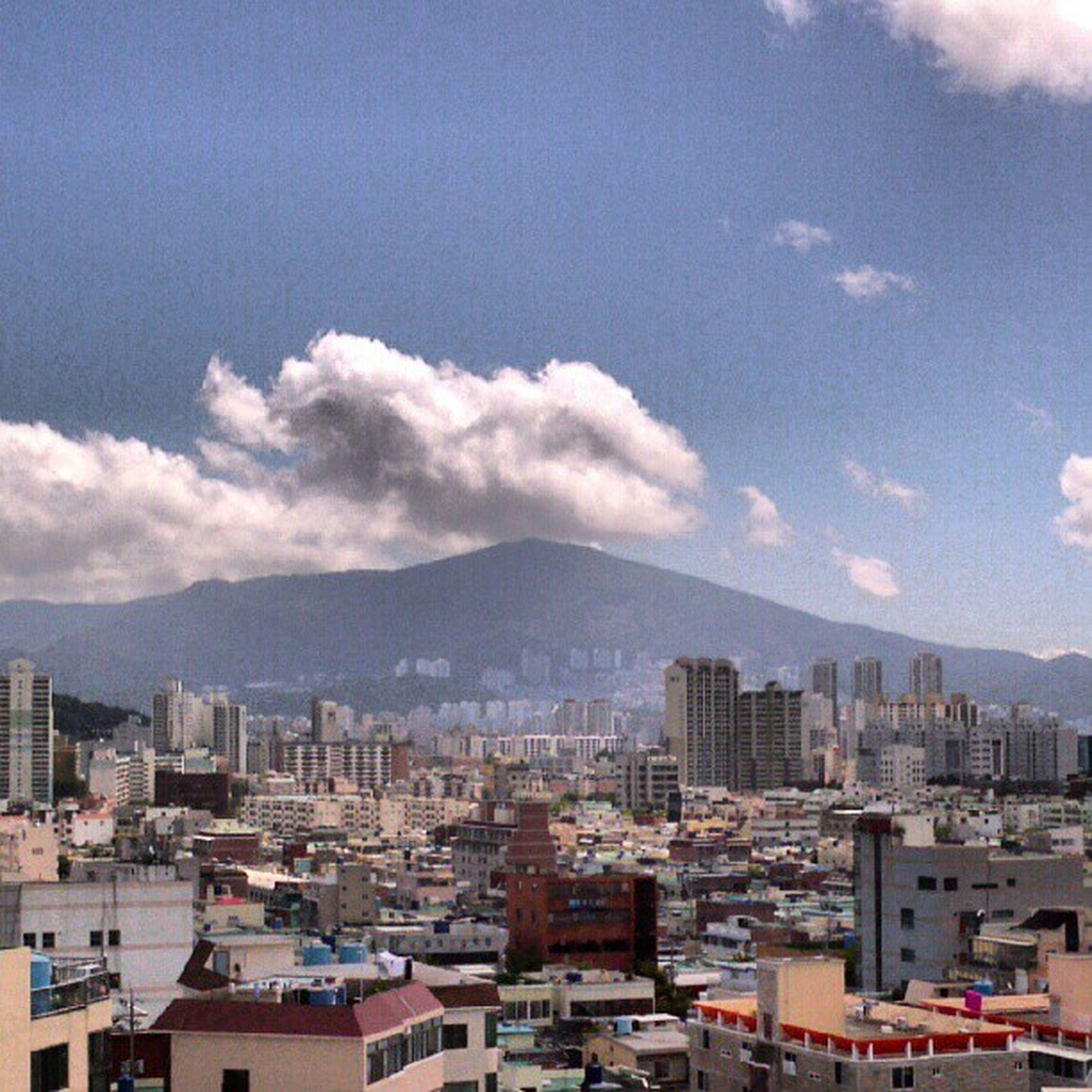 building exterior, architecture, cityscape, built structure, city, sky, crowded, residential district, mountain, residential building, cloud - sky, residential structure, cloud, high angle view, mountain range, skyscraper, city life, day, outdoors, no people