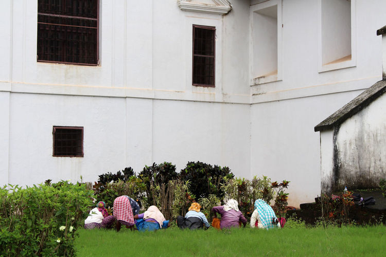 Rear view of people sitting outside building