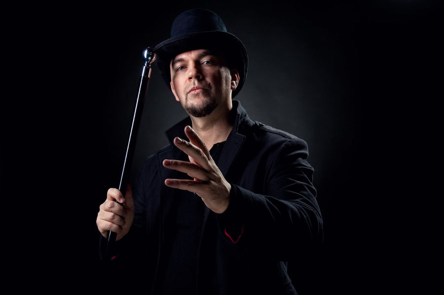 Handsome man wearing black hat and jacket holding stick over black background Artist Artistic Handsome Man Hat Magical Males  Man Wizard Adult Beard Black Background Caucasian Entertainment Gangster Gesture Headdress Indoors  Magic Magician Male One Person People person Stick Studio Shot