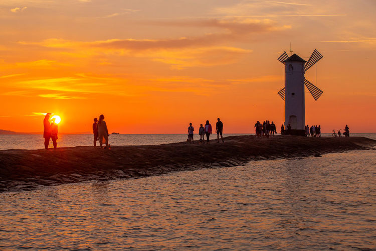 Baltic Sea Stawa Mlyny Beach Beauty In Nature Cloud - Sky Crowd Group Of People Horizon Over Water Land Large Group Of People Leisure Activity Lifestyles Men Nature Orange Color Outdoors Real People Scenics - Nature Sea Sky Sunset Vacations Water