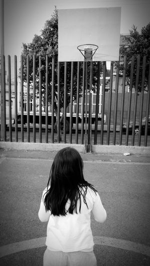 Rear view of girl standing on road