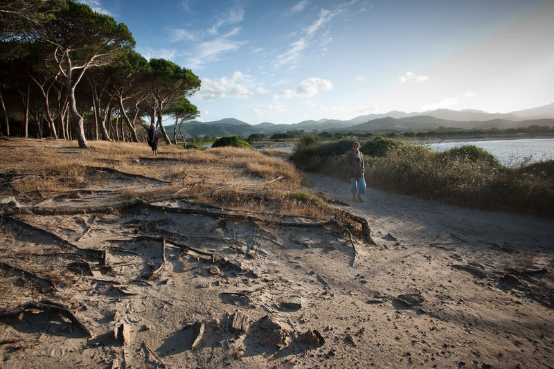 A girl strolling through the countryside of sardina Beach Beauty In Nature Girl Hiking Landscape Nature One Person Outdoors Sand Shadows Sky Sunset Tree Water Woman