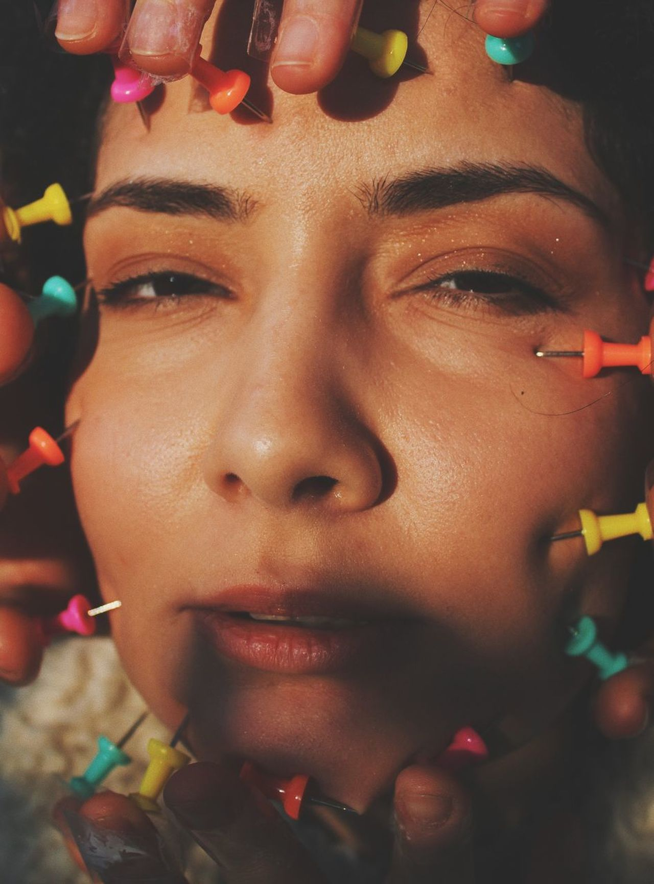 Close-Up Portrait Of Woman With Thumbtacks On Face