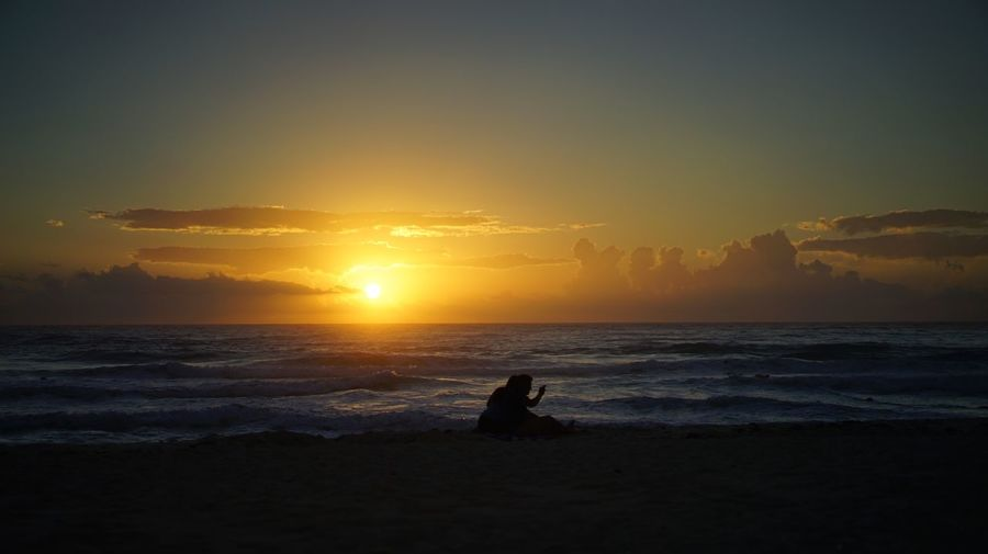 Silhouette couple sitting on shore at beach against sky during sunset