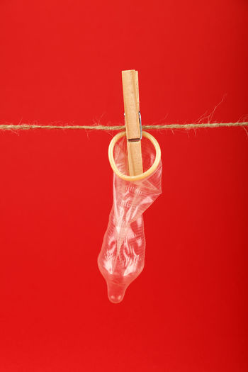 Open condom with cloth pin on washing line over red background Contraceptive Laundry Medicine Close-up Clothes Pin Colored Background Concept Condom Contraception Copy Space Creativity Health Care Health Care And Medical Health Care Concept Healthcare And Medicine Interception Open Prevention Protection Red Red Background Safe Safety Single Object Studio Shot