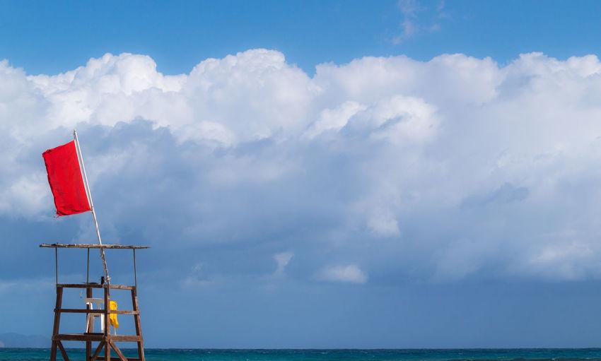 Lifeguard chair against cloudy sky
