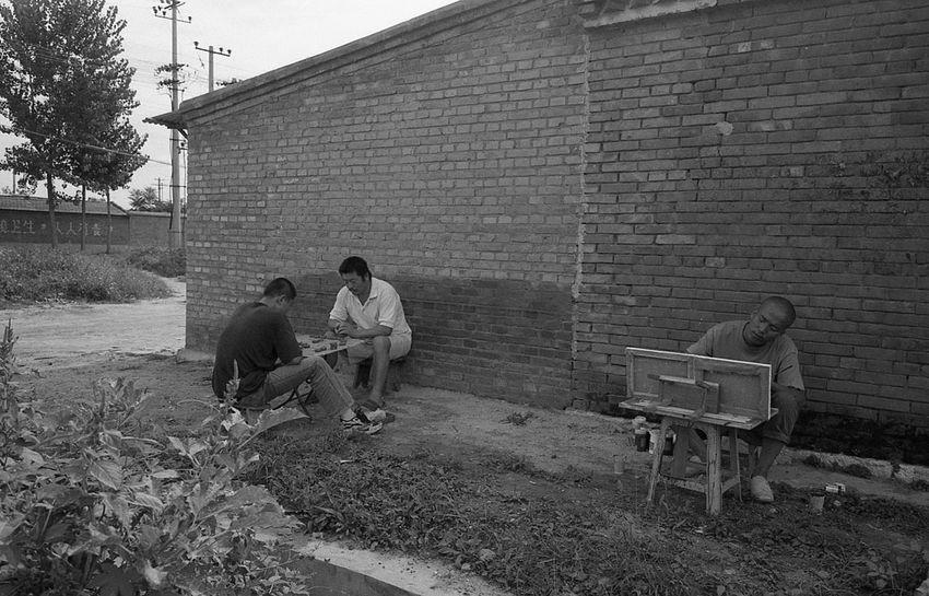 刘宁在村头画画 旁边的村民在下象棋。开始我以为刘在写生,近前一看才知,刘的画布上丝毫未呈现周围事物。他只是喜欢在室外画画。现在刘也已离开宋庄多年。2004年 12820764 1613 5093 10909308