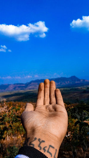 Cropped hand against blue sky