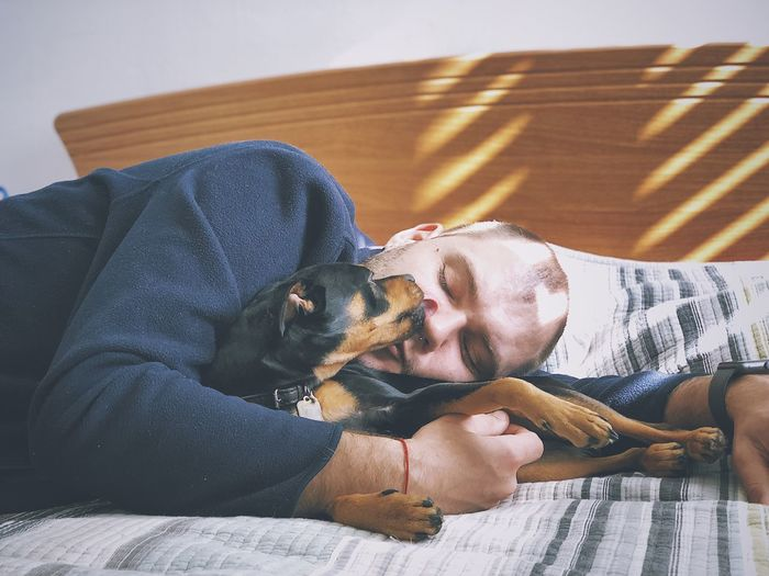 Man kissing dog while lying on bed at home
