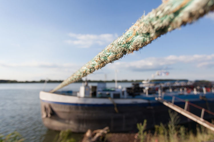 anchored boat tied with heavy duty rope Anchor Anchored Background Boat Day Lake Moored Nautical Vessel No People Outdoors River Rope Rusty Sail Secured Shipping  Shore Sky Tied Transportation Transportation Travel Water Weathered Wire