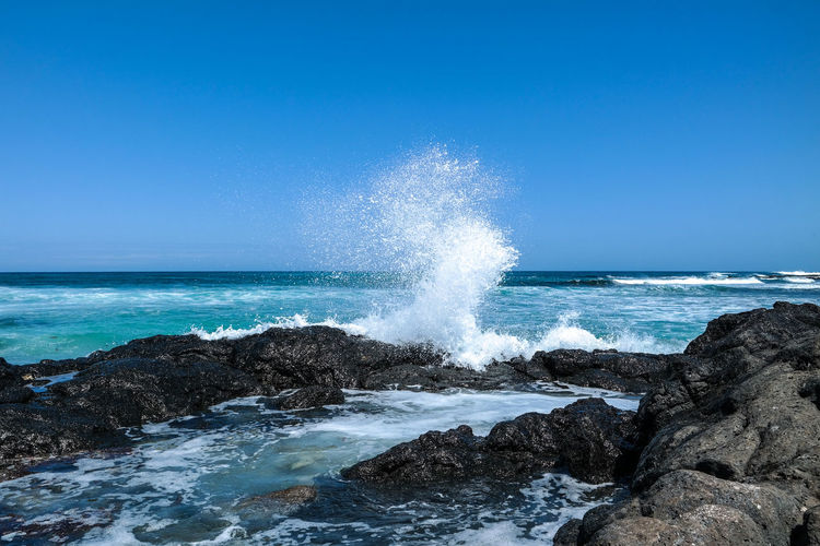 Sea waves splashing on rocks against blue sky