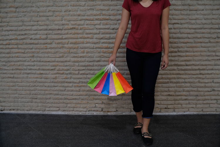 Low Section Of Woman With Colorful Shopping Bags Standing Against Wall