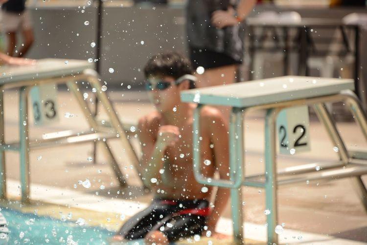 Drops in mid-air against teenage boy sitting at poolside by diving platform