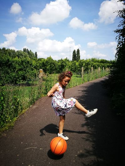 Girl kicking ball on road during sunny day