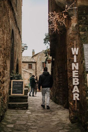 Rear view of people walking in alley amidst buildings