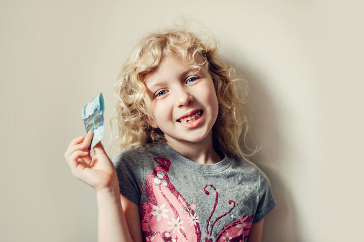 Caucasian blonde girl showing her missing tooth in a mouth and holding money from tooth fairy.