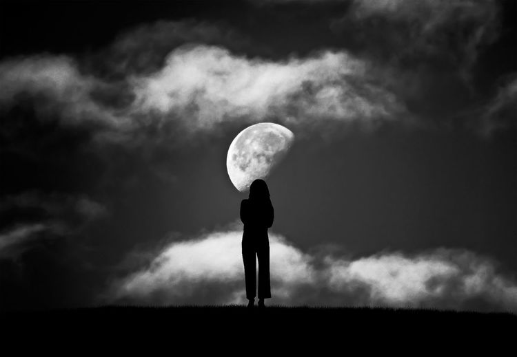 Silhouette Woman Standing On Field Against Moon In Sky