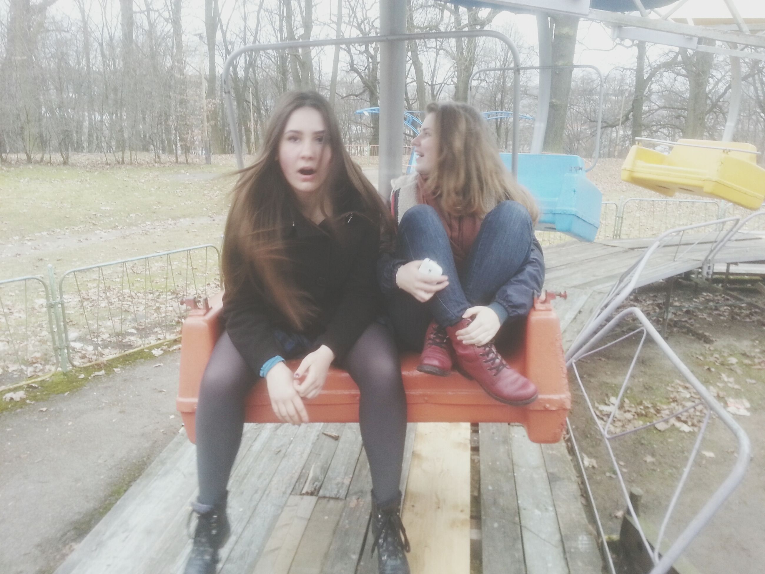 lifestyles, leisure activity, casual clothing, young adult, person, young women, full length, tree, sitting, looking at camera, long hair, front view, standing, portrait, park - man made space, smiling, togetherness