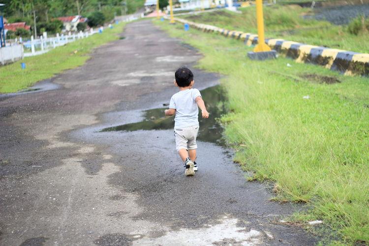 Rear view of boy running on grass