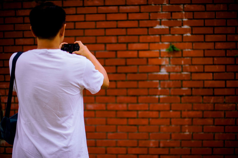 Rear view of man photographing against brick wall