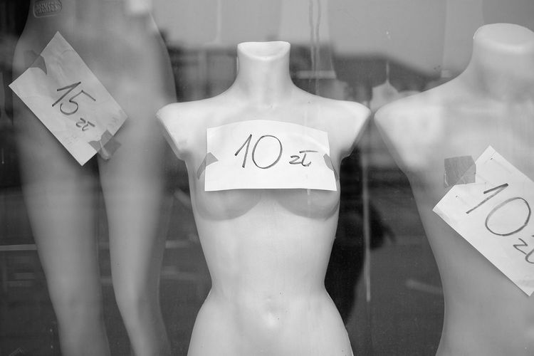 Close-up of mannequins with labels seen through window
