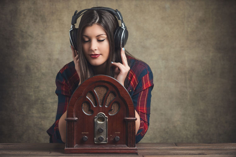 Young woman with an old radio and a modern headphone Background Beautiful Woman Brunette Caucasian Copy Space Girl Headphones Indoors  Leisure Activity Listening Music Old-fashioned One Person Opposites People Portrait Portrait Of A Woman Radio Retro Styled Smile Table Technology Vintage Woman Young Women EyeEmNewHere The Portraitist - 2017 EyeEm Awards EyeEm Selects The Creative - 2018 EyeEm Awards International Women's Day 2019