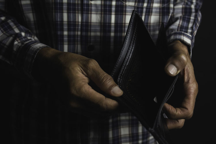Midsection of man holding empty wallet