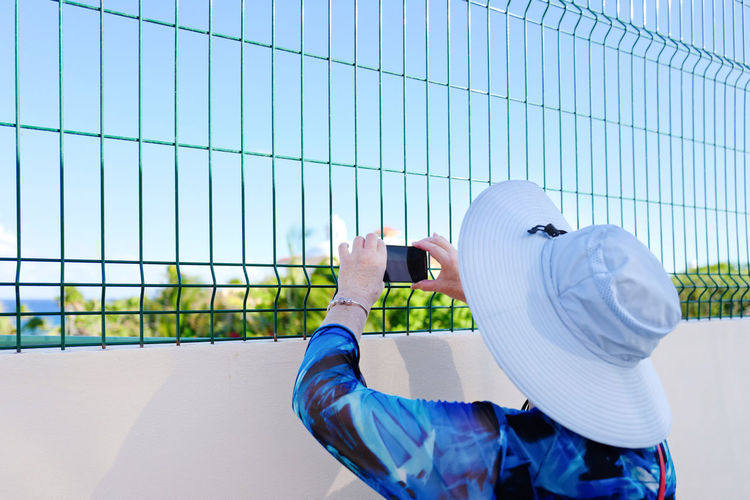 Rear view of man using mobile phone against fence