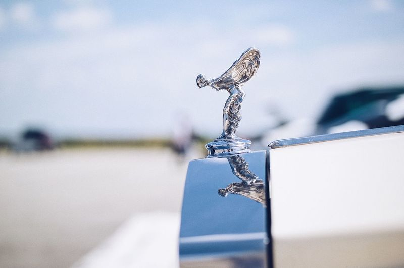 Silver statue of a famous age 🚘... Wealth Wings Vintage Car Detail Silver - Metal Rollsroyce Logo Design Expensive Cars Vintage Car Car Expensive Rich Limousine Rolls Royce Sculpture Statue Logo Focus On Foreground Close-up No People Day Selective Focus Still Life Decoration Craft Art And Craft Metal Detail Container Blue