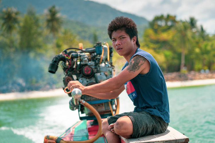 Steering the Way Transportation Longtail Boat Engine Steering One Person Real People Mode Of Transportation Young Adult Nature Looking At Camera Sitting Nautical Vessel Boat Fast Thailand Jungle Beach Colorful Tattoo Captain Shorts Travel Destinations Travelling Thai Wind