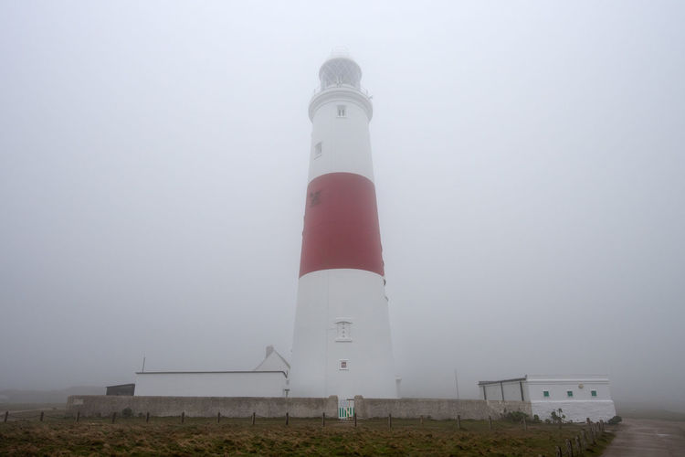 Portman Bill Lighthouse during heavy fog weather conditions on the Isle of Portland, Dorset, England. Dorset Bad Weather Famous Location Foggy Foggy Weather Jurassic Coast Lighthouse Low Cloud Portland Portland Bill Portland Bill Lighthouse Portland Island Thick Fog Weymouth Fog Guidance Architecture Sky Building Exterior Built Structure Building Tower Nature No People Direction Protection Security Day Safety Low Angle View Outdoors Tall - High