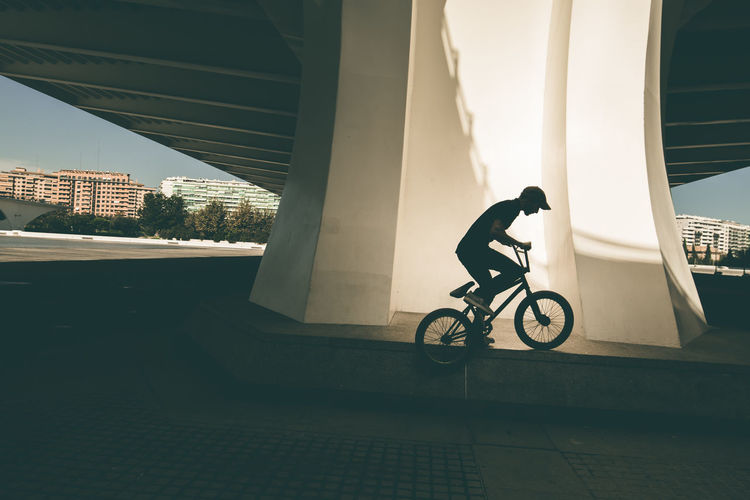 Side view of man riding bicycle on building