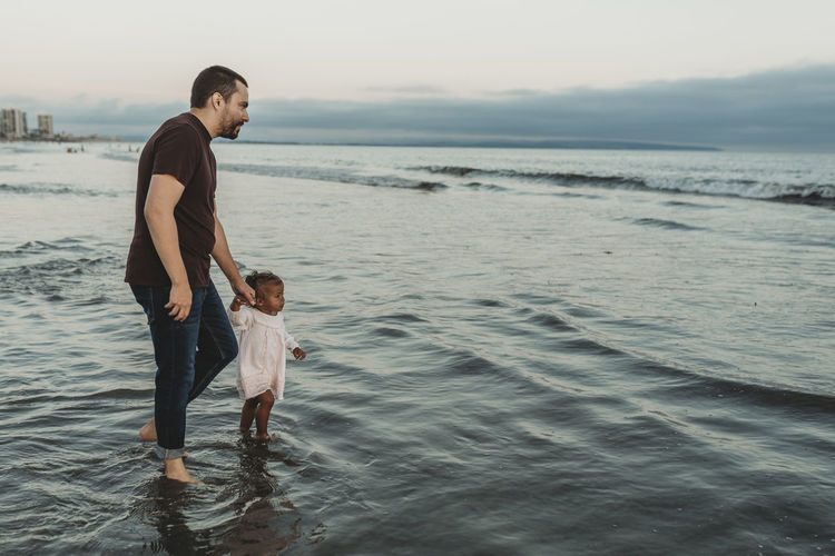 Full length of father and son at beach against sky