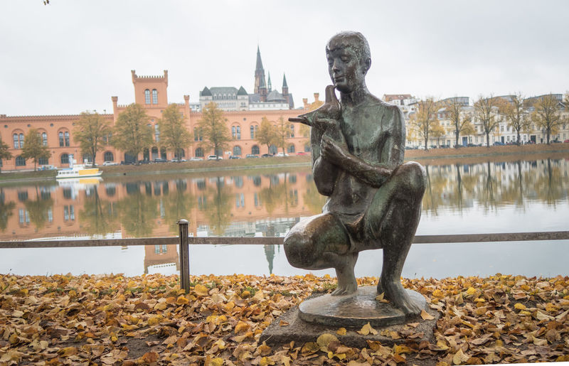 Golden statue of Schwerin Castle, Schwerin, Germany Sculpture Art And Craft Representation Water Statue Architecture Human Representation Creativity Day Built Structure Nature Sky No People Lake Travel Destinations Male Likeness Building Exterior Plant Outdoors