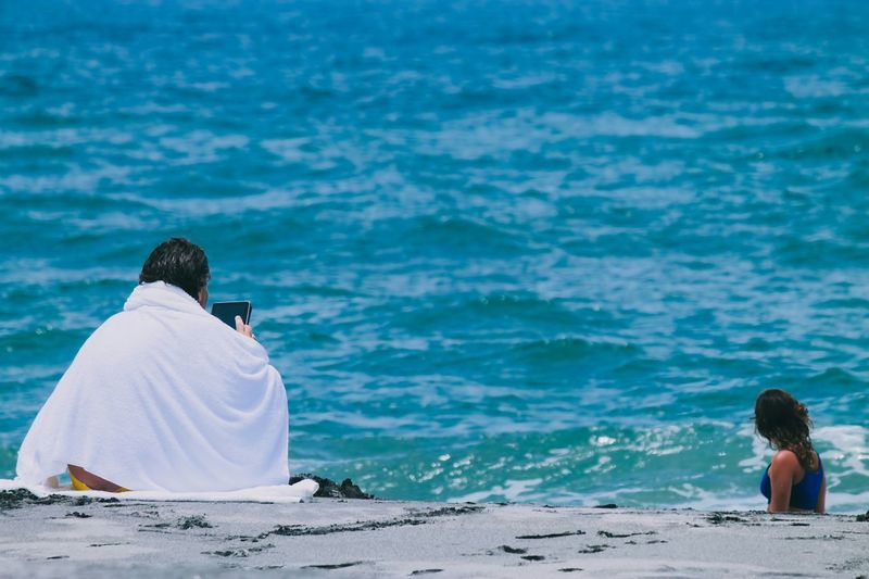 Person Wrapped In Towel Using Tablet With Woman In Background At Beach