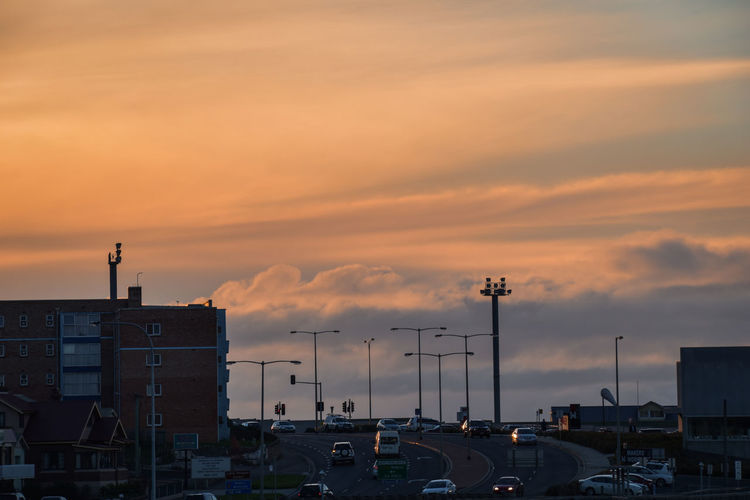 Cars on road by buildings against orange sky