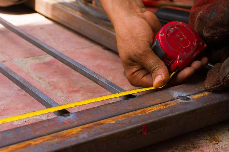 Cropped hand measuring metal