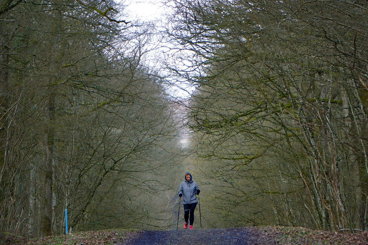 Full length rear view of man standing in forest