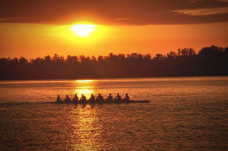 Silhouette People Rowing Boat Against Orange Sky During Sunrise