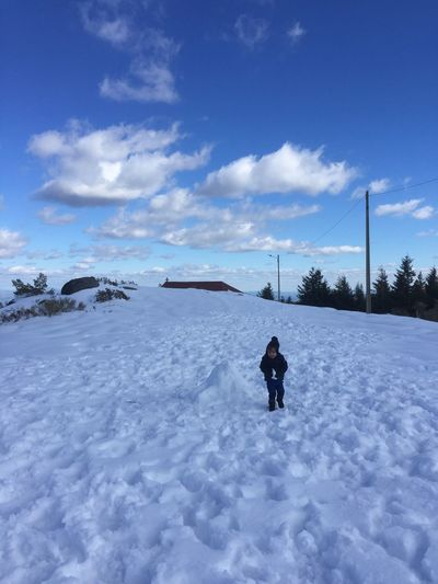 Boy walking on snow covered field against blue sky