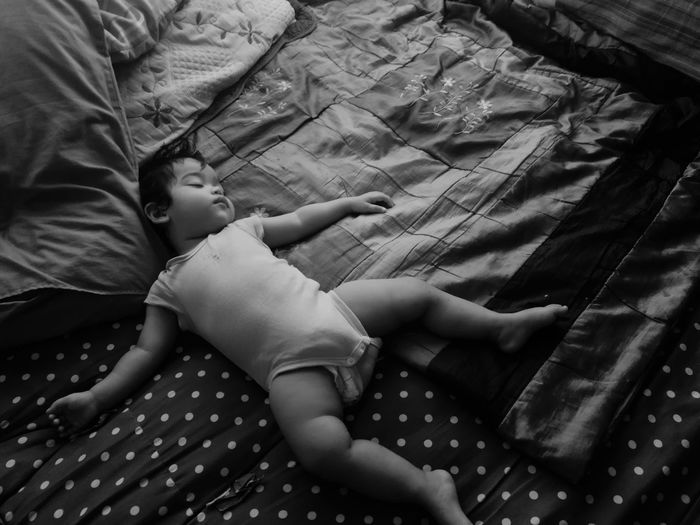 High angle view of child sleeping on bed at home